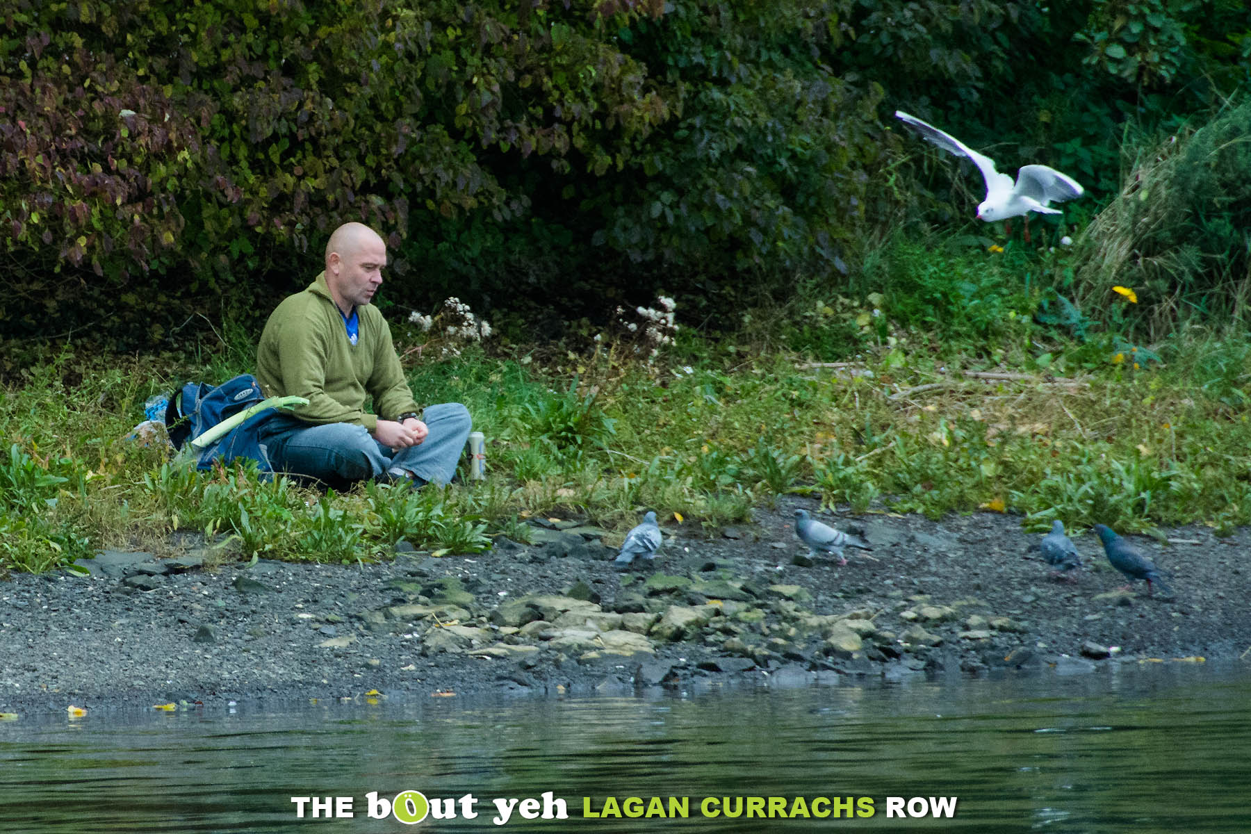 A man sits on the side of the River Lagan feeding birds, as seen from the Bout Yeh Lagan Currachs row - photo 9219.