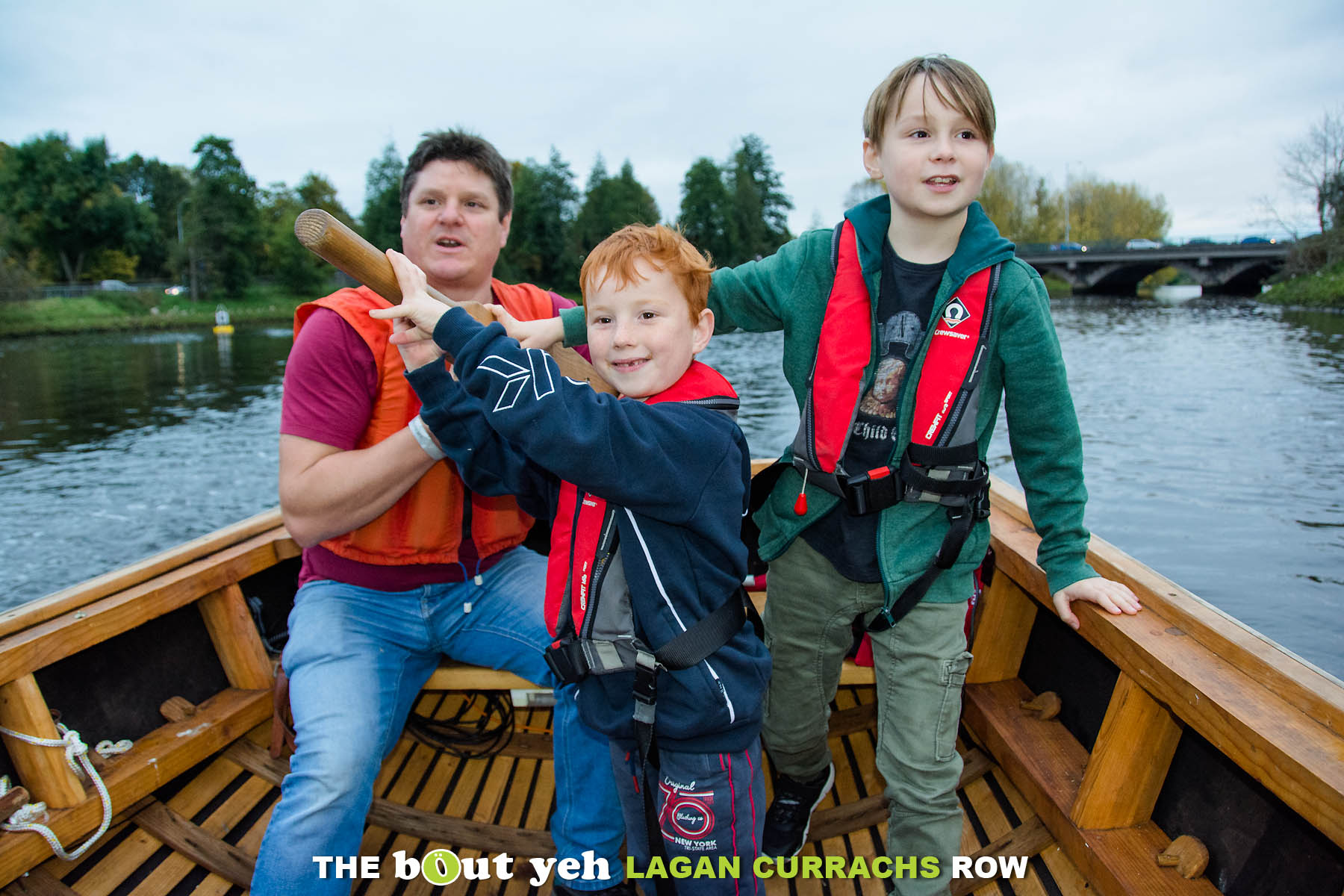 Lagan Currachs team member Tim shows young boys how to steer a currach on the River Lagan, Belfast - photo 9245.