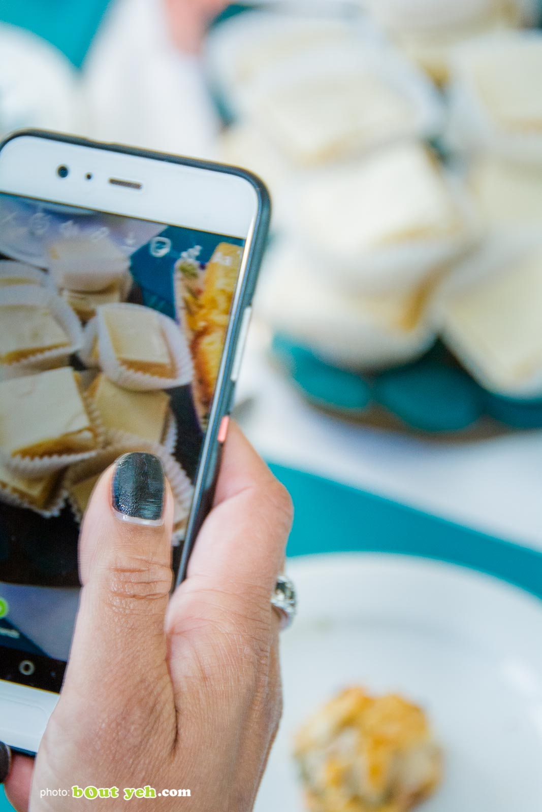 Hand on smartphone displaying photo of food at the Bout Yeh Brexit Mad Hatters Tea Party photo 9266 - Bout Yeh photographers Belfast