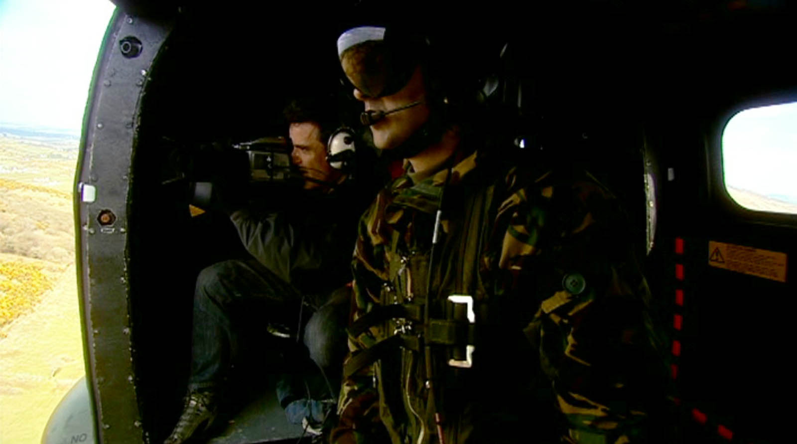 Video production for BBC Worldwide of Magnum photographer Donovan Wylie - Donovan with helicopter crew British army chinook helicopter flying above South Armagh filmed by a director at Bout Yeh video production Belfast, Northern Ireland