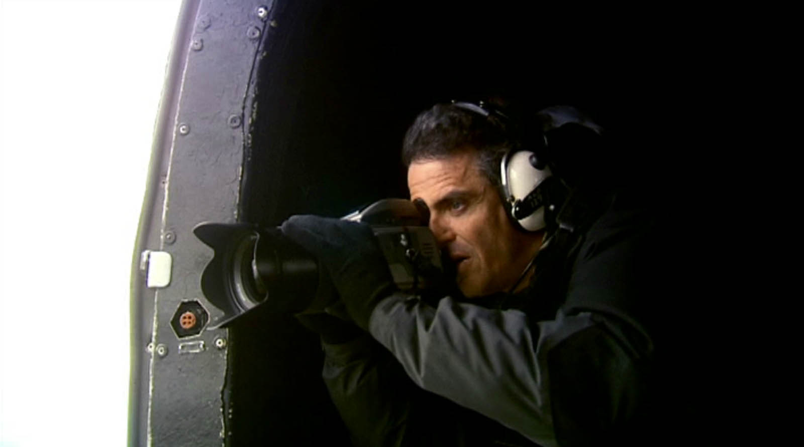 Video production for BBC Worldwide of Magnum photographer Donovan Wylie - Donovan photographing from British army helicopter filmed by a director at Bout Yeh video production Belfast, Northern Ireland