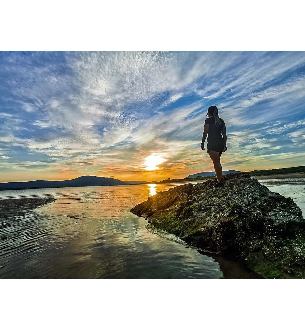 Woman stands on rocks while looking at sunset over lake in the Mourne Mountains, Northern Ireland - photo 1313