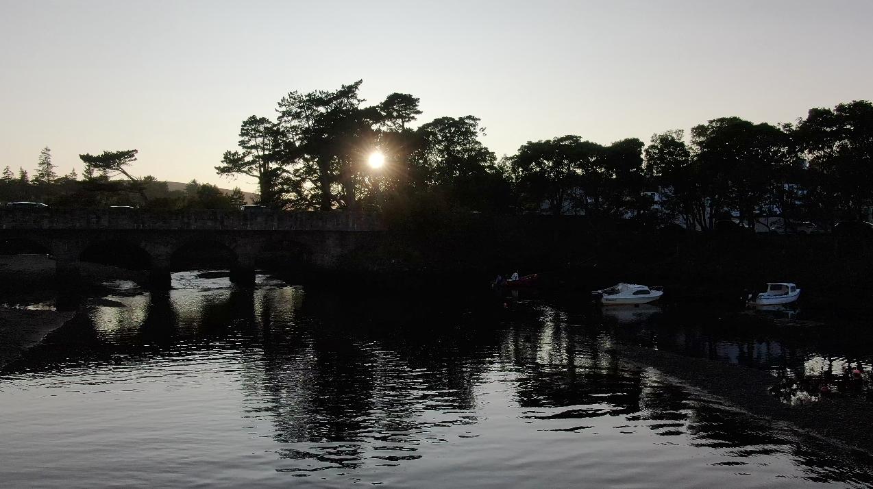 Setting sun shines through trees above bridge and River Dun at Cushendun, Glendun