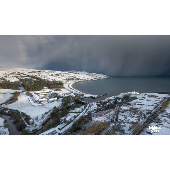 Aerial photograph of Cushendun village and Cushendun Bay, Northern Ireland, in winter under snow and storm clouds by Bout Yeh photographers Belfast. Photo 230121