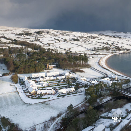 Aerial photograph of Cushendun village and Cushendun Bay, Northern Ireland, in winter under snow and storm clouds by Bout Yeh photographers Belfast. Left side of photo 230121