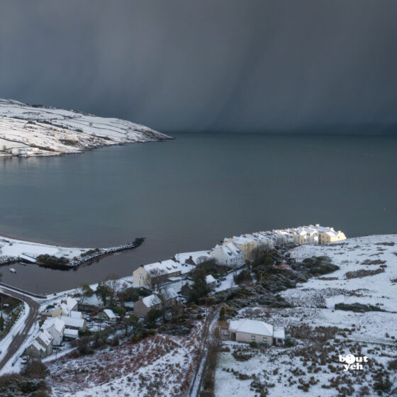 Aerial photograph of Cushendun village and Cushendun Bay, Northern Ireland, in winter under snow and storm clouds by Bout Yeh photographers Belfast. Right side of photo 230121