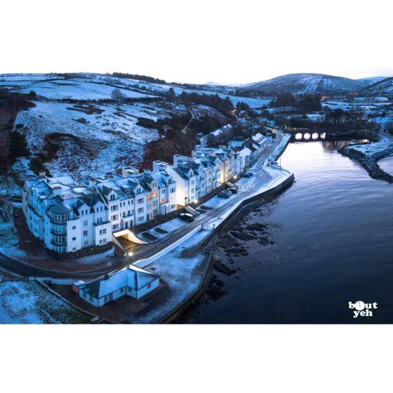 Aerial photograph of Bay Apartments Cushendun, Northern Ireland, in winter under snow by Bout Yeh photographers Belfast. Photo 231121